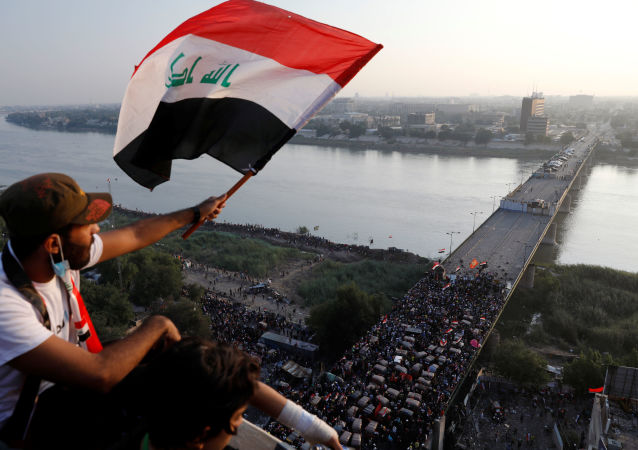 A demonstrator holds an Iraqi flag as he sits on a building during an anti-government protests in Baghdad, Iraq October 30, 2019