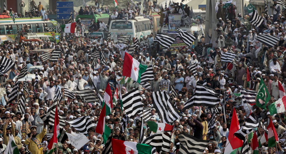 Supporters of religious and political party Jamiat Ulema-i-Islam-Fazal (JUI-F) wave flags as they listen to the speech of their leaders while heading towards Islamabad city, during what they call Azadi March (Freedom March) to protest the government of Prime Minister Imran Khan in Lahore, Pakistan October 30, 2019