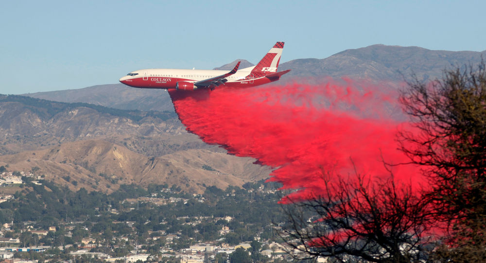 A plane drops fire retardant on the Maria Fire in the early morning in Santa Paula