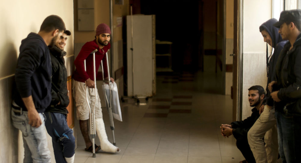 Palestinian men wounded at the Israel-Gaza border wait after receiving treatments at the Shifa Hospital in Gaza City