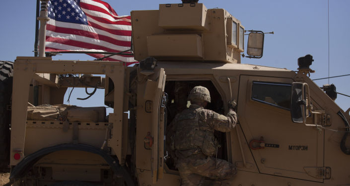 In this Sept. 8, 2019, photo, a U.S. soldier climbs into an armored vehicle during the first American-Turkish joint patrol in the so-called safe zone on the Syrian side of the border with Turkey near Tal Abyad, Syria