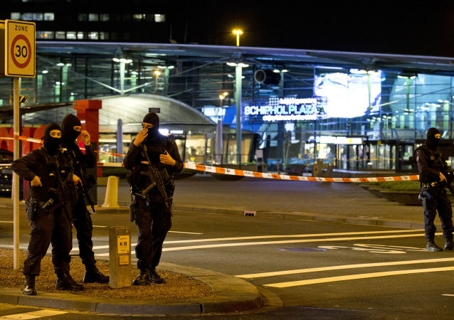 Hooded security forces guard a part of Schiphol Aiport in Amsterdam, Netherlands