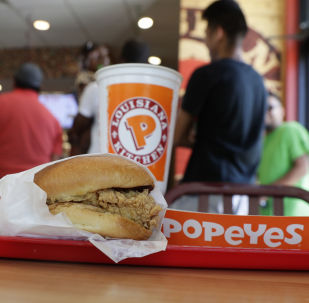 A chicken sandwich sits on a table at a Popeyes as guests wait in line, Thursday, Aug. 22, 2019, in Kyle, Texas