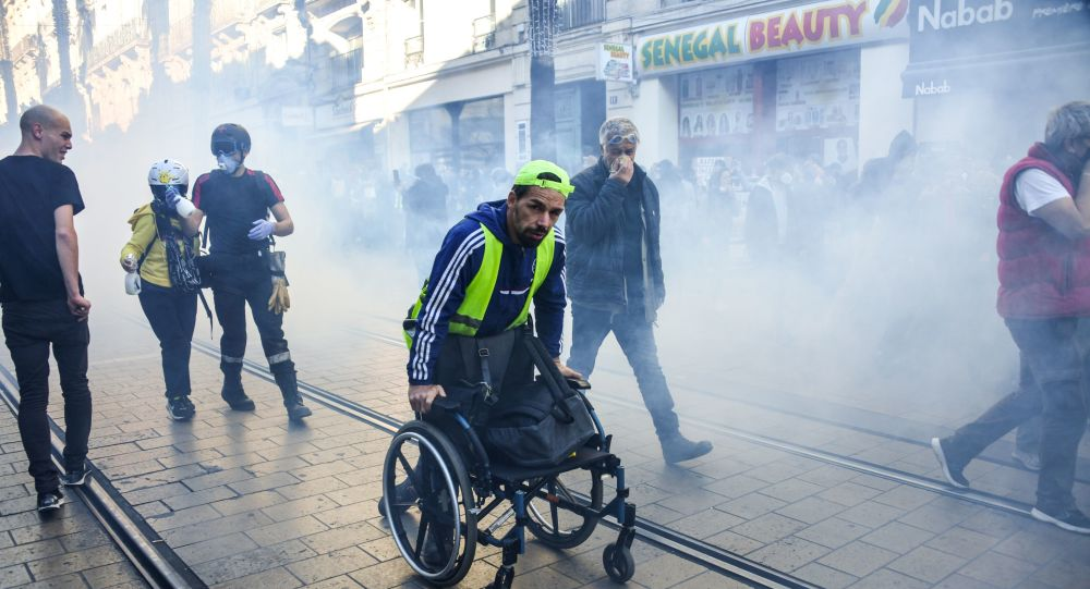 A man pushes his wheelchair away from teargas on Novemebr 9, 2019 in the center of Montpellier, southern France, during a demonstration as part of an nationwide anti-government protest called by the yellow vest movement (gilets jaunes).