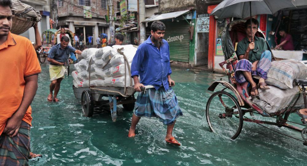 Bangladeshi men pull a loaded cart through a waterlogged street after heavy rainfall in Dhaka, Bangladesh, Saturday, May 21, 2016.