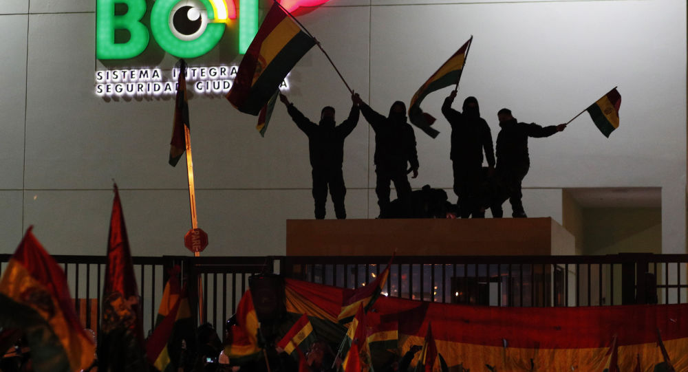 Police officers standing on the rooftop of a security booth at a police station wave Bolivian flags in front of protesters in La Paz