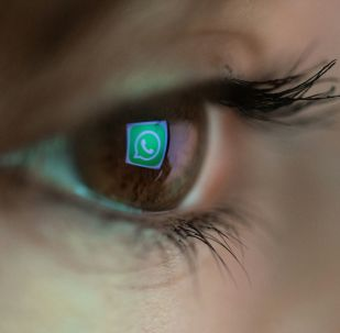 An illustration picture taken on March 22, 2018 in Paris shows a close-up of the WhatsApp logo in the eye of an AFP staff member posing while she looks at a flipped logo of WhatsApp