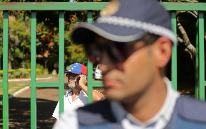 A man wearing a Venezuelan cap stands behind a fence on the grounds of Venezuelan embassy in Brasilia, Brazil, November 13, 2019.