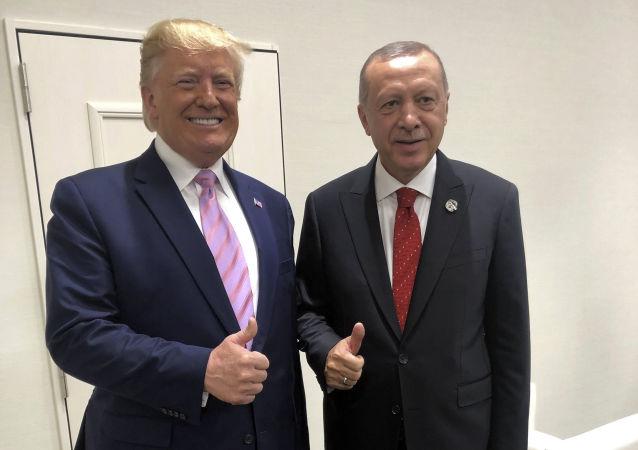 Turkey's President Recep Tayyip Erdogan, right, and U.S President Donald Trump gesture during the G-20 summit in Osaka, Japan, Friday, June 28, 2019