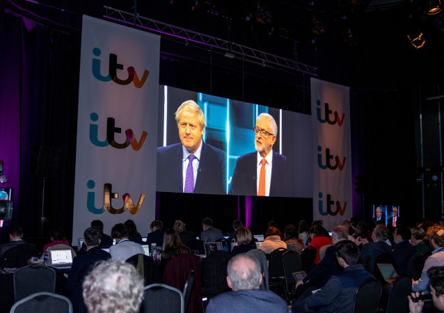 Boris Johnson and Jeremy Corbyn are seen on a screen as journalists watch tonight's debate in the 'Spin Room' ahead of general election in London, Britain, November 19, 2019