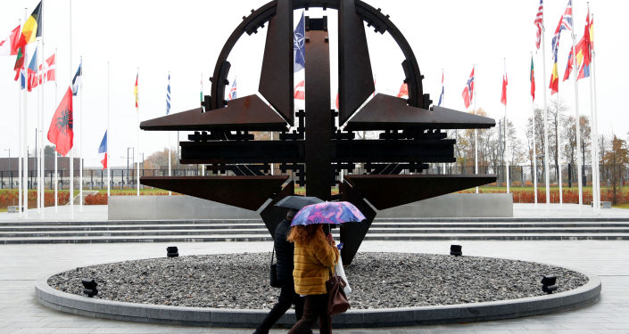 People hold umbrellas outside NATO headquarters in Brussels, Belgium, November 26, 2019