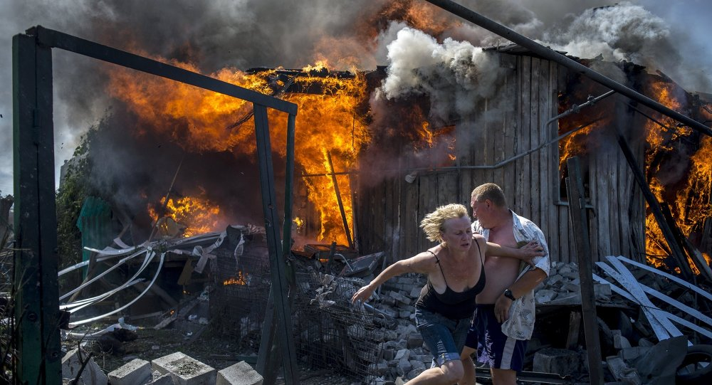 Local residents flee from a burning home hit by an air strike by the Ukrainian armed forces in Lugansk.