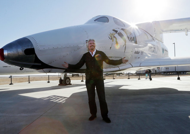 British entrepreneur Richard Branson poses with SpaceShipTwo at a Virgin Galactic hangar at Mojave Air and Space Port in Mojave, Calif.