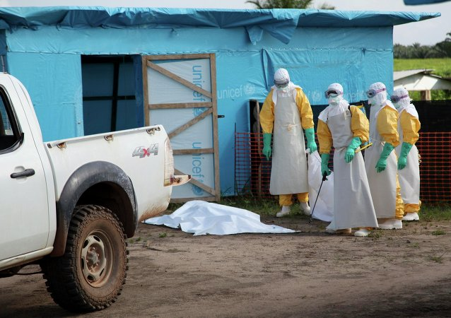 Medical workers by an isolation tent housing those infected with Ebola, Liberia.
