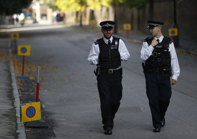 British police officers patrol the road leading to Kensington Palace