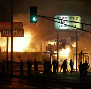 People gather around the burning stores in Ferguson