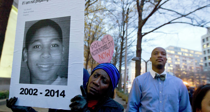 A protester holds a picture of Tamir Rice, the boy fatally shot by a rookie police officer