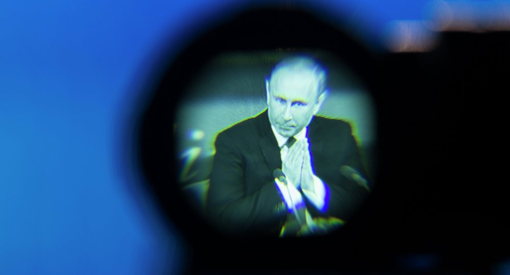 Russian President Vladimir Putin seen gesturing in a camera viewfinder during his annual news conference in Moscow, Russia, Thursday, Dec. 18, 2014. The Russian economy will rebound and the ruble will stabilize, Russian President Vladimir Putin said Thursday at his annual press conference, he also said Ukraine must remain one political entity, voicing hope that the crisis could be solved through peace talks.