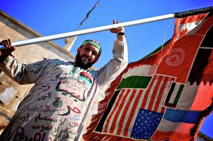 A man holds a flag of countries involved in the Libyan Civil War.