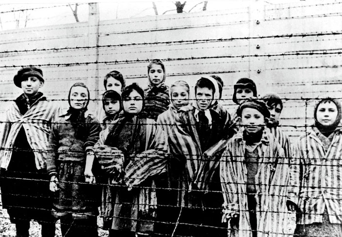 Un groupe d'enfants portant des uniformes de camp de concentration derrière des barbelés dans le camp de concentration nazi d'Oswiecim (Auschwitz)