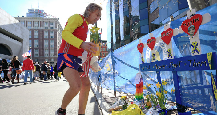 A runner pays his respects at a makeshift memorial honoring to the victims of the 2013 Boston Marathon bombings.