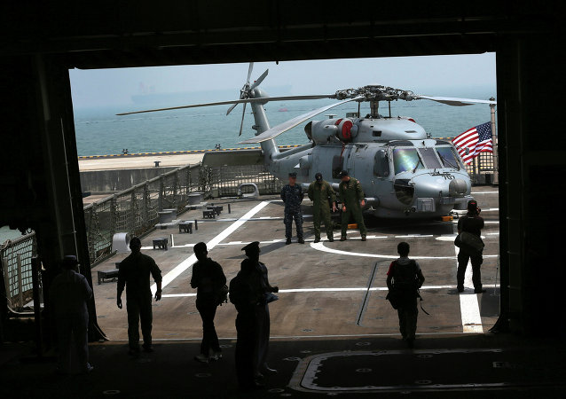 U.S. Navy officers are silhouetted against the flight deck of the U.S. Navy ship USS Freedom (LCS 1) berthed at the Changi Naval Base