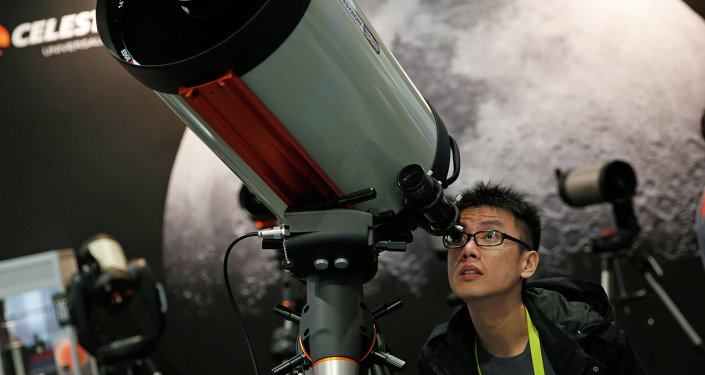 Kei Yuen Hung looks through a telescope at the Celestron booth during the International CES Friday, Jan. 9, 2015, in Las Vegas.