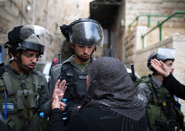 A Palestinian woman argues with Israeli border police near the Lions Gate in the Old City of Jerusalem