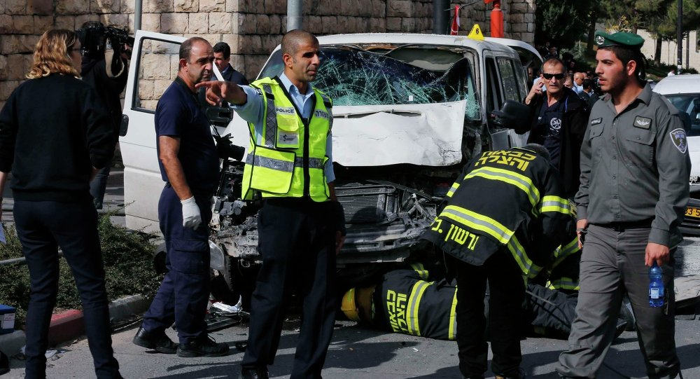 An Israeli police officer gestures in front of the vehicle of a Palestinian motorist who rammed into pedestrians at the scene of the attack in Jerusalem November 5, 2014