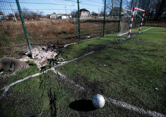 A ball is seen near a crater caused by shelling at a school's soccer field in Donetsk, eastern Ukraine, November 6, 2014