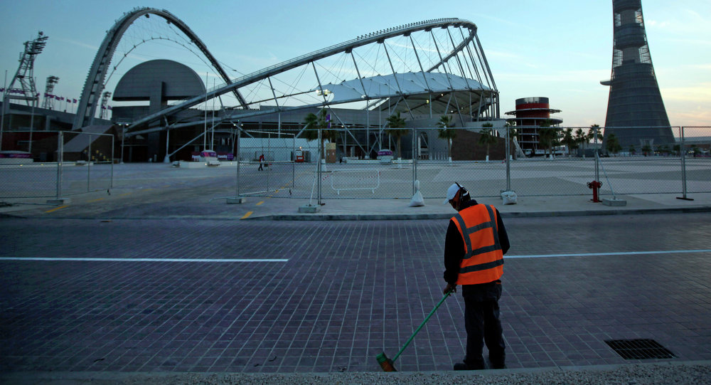 In this Jan. 3, 2011 file photo, a worker cleans the road outside Khalifa sport complex in Doha, Qatar