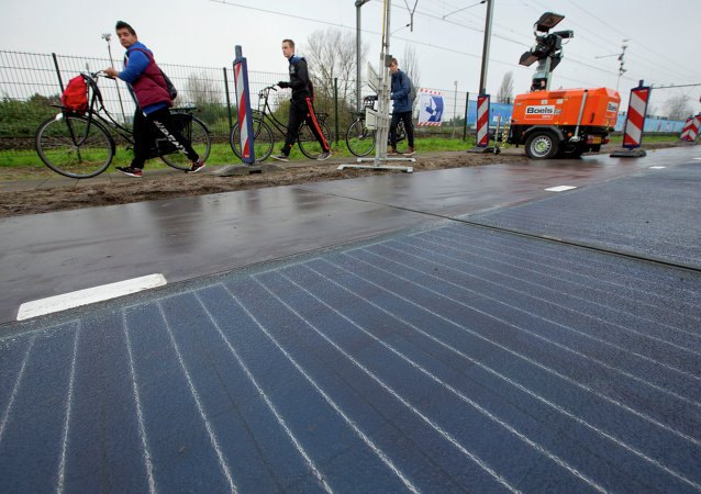 Bicyclists are forced to use the sidewalk as they pass a stretch of bicycle path where a solar panel roadway is being constructed in Krommenie, north of Amsterdam, Netherlands, Tuesday, Nov. 11, 2014