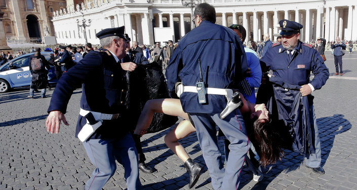 talian police officers carry away a Femen activist during a protest in St. Peter's Square at the Vatican, Friday, Nov. 14, 2014