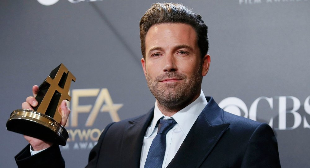 Actor Ben Affleck poses backstage with the Hollywood film award, which he accepted on behalf of the creators, for Gone Girl during the Hollywood Film Awards in Hollywood, California