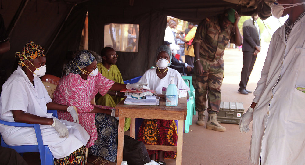 Health care workers at a screening center for the Ebola virus await patients at the border village of Kouremale, Mali