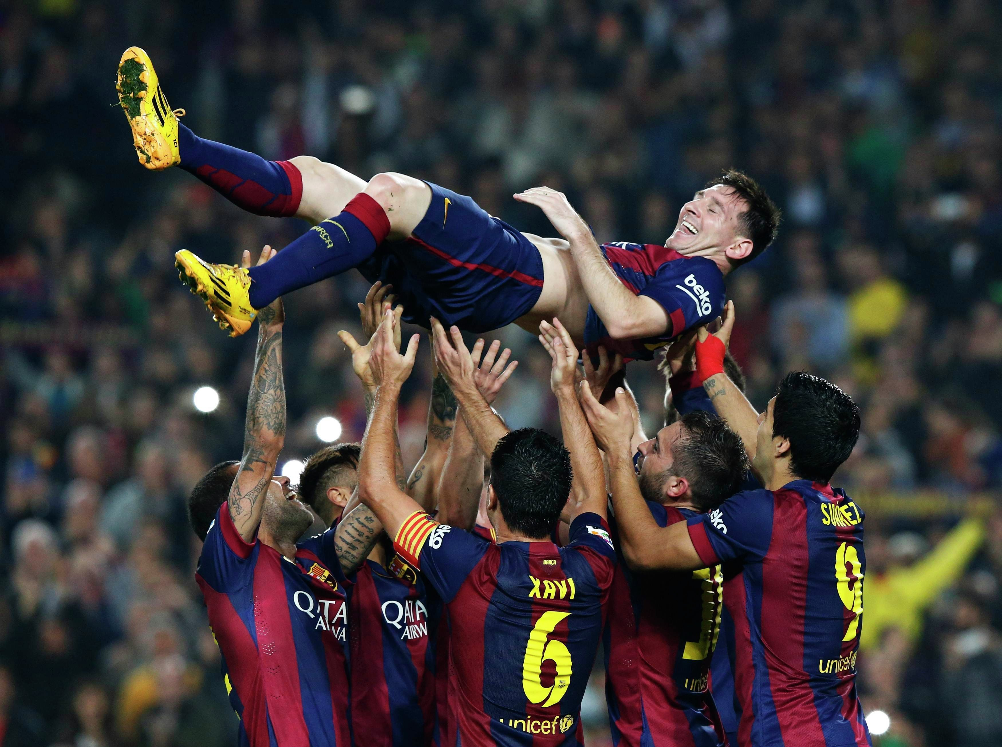 Barcelona's Lionel Messi celebrates his second goal with teammates during their Spanish first division soccer match against Sevilla at Nou Camp stadium in Barcelona November 22, 2014