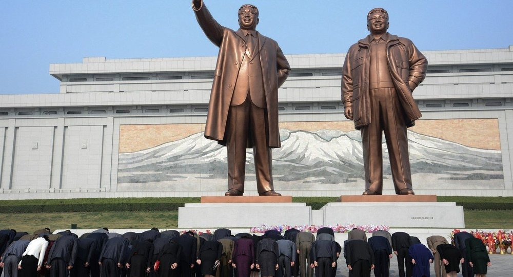 Pyongyang, North Korea: North Koreans bow in-front of statues of the former leaders Kim Il-sung (left) and Kim Jong-il (right) at the Mansudae Grand Monuments