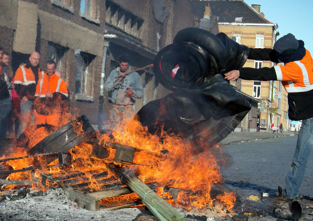 A man throws rubber tires onto a fire during a demonstration in the Port of Antwerp in Antwerp, Belgium