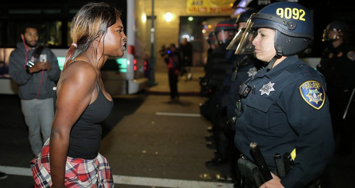 Amanda Ashe of Oakland, left, faces off with a police officer during the second night of demonstrations in Emeryville, California, following the grand jury decision in the shooting of Michael Brown in Ferguson, Missouri