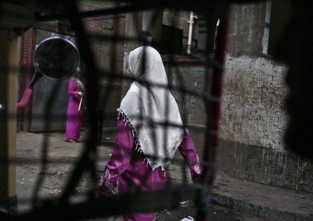 An Egyptian woman seen from a motorized rickshaw walks on a street, near the home of 13-year-old Sohair el-Batea who died undergoing the procedure of female genital mutilation