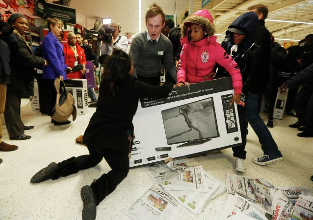 Shoppers wrestle over a television as they compete to purchase retail items on Black Friday at an Asda superstore in Wembley, north London November 28, 2014