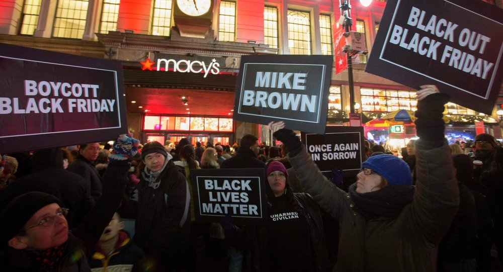 Protesters hold signs aloft outside Macy's before the kick off of Black Friday sales in New York November 27, 2014