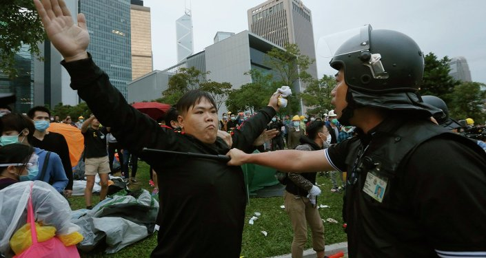 A pro-democracy protester blocks a riot policeman during a clash outside the government headquarters in Hong Kong