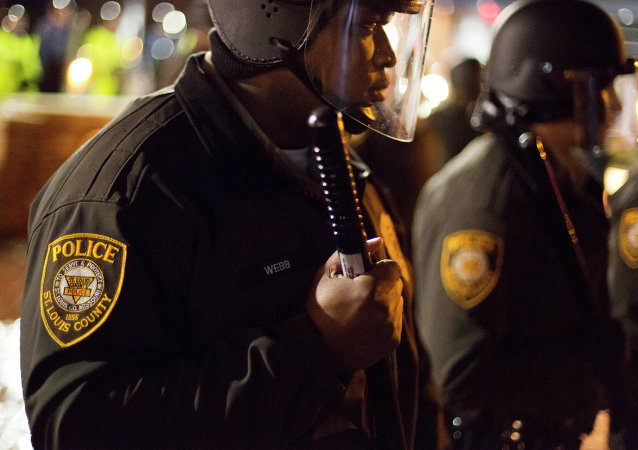 Police stand guard during a demonstration outside the Ferguson Police Department, Saturday, Nov. 22, 2014, in Ferguson, Mo.