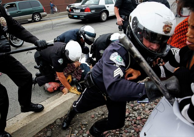An LAPD motorcycle officers uses his baton to push back demonstrators as his colleagues detain a man during a rally against the Missouri grand jury's decision