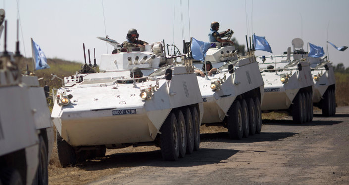 Armored vehicles from the U.N. peacekeepers of the United Nations Disengagement Observer Force, also known as UNDOF wait to cross from the Israeli controlled Golan Heights to Syria
