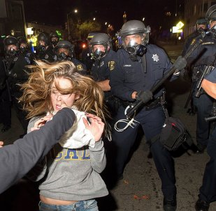 A protester flees as police officers try to disperse a crowd comprised largely of student demonstrators during a protest against police violence in the U.S., in Berkeley, California early December 7, 2014
