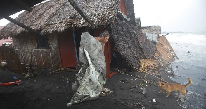 A Filipino man carries a dirty plastic sheet from his house after strong waves from Typhoon Hagupit