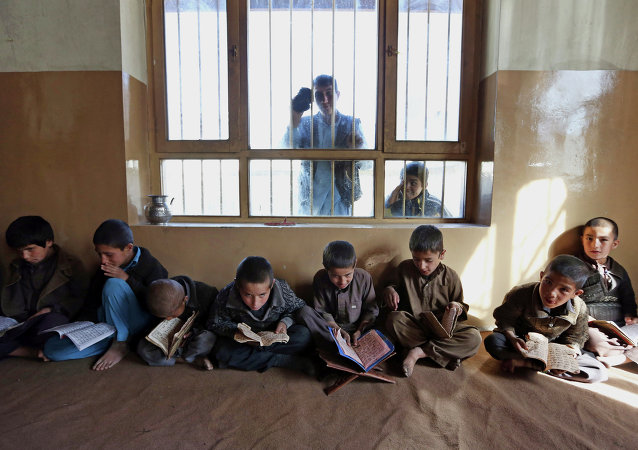 In this file photo taken Tuesday, Nov. 11, 2014, Afghan children recite the Quran, Islam's holy book, at a local Madrassa, or seminary, in Kabul, Afghanistan