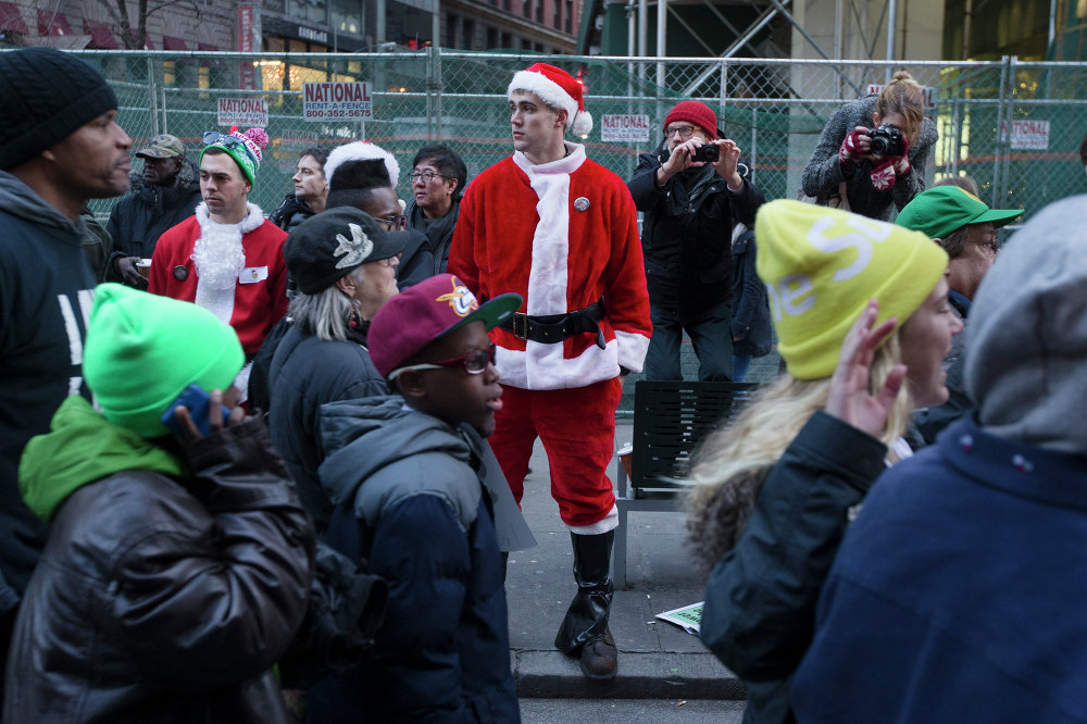 A SantaCon reveler watches as demonstrators march in New York, Saturday, Dec. 13, 2014